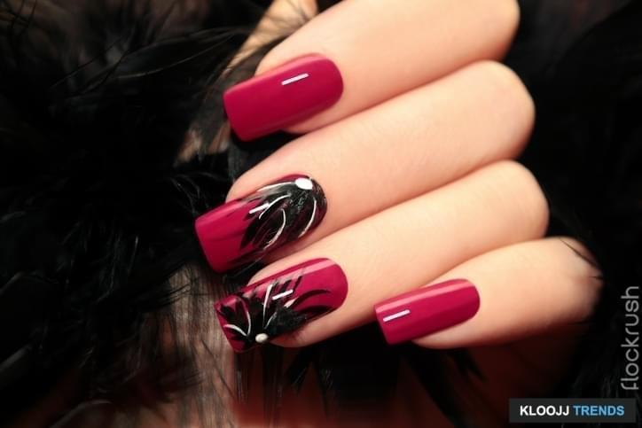 Burgundy manicure with design on the nails and feathers.