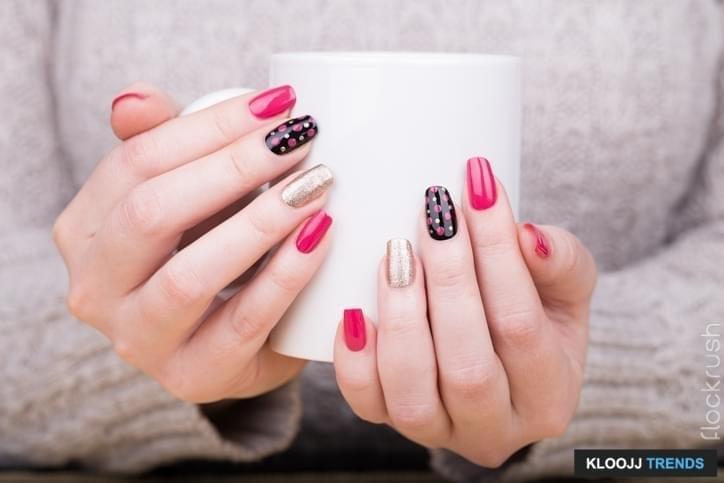 Beauty treatment photo of nice manicured woman fingernails. Very nice feminine nail art with nice pink, gold and black nail polish.