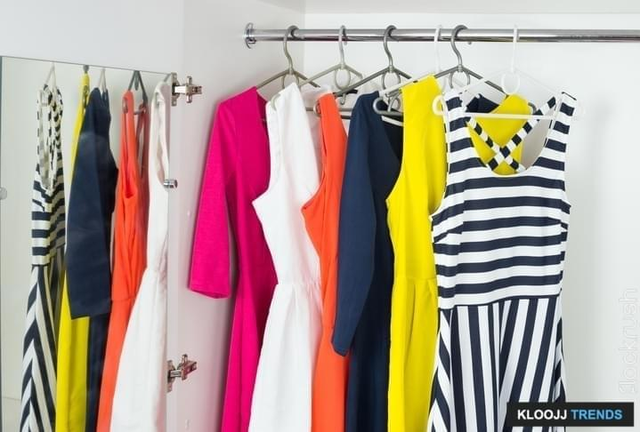 a series of bright modern fashion women's dresses on hangers in a white cupboard for summer and spring