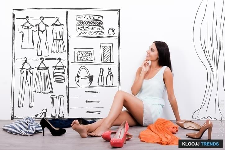 Thoughtful young woman in dress looking at the sketch on the wall while sitting on the floor with clothes and shoes laying around her