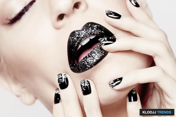 Closeup of sexy beautiful model with black lipstick and silver glitter sparkles, with matching manicure, hands on face, very fashion, high end, trendy makeup and pose.