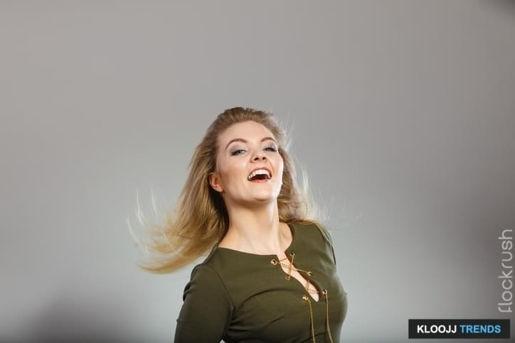 Fashionable outfit ideas, trendy clothes concept. Attractive blonde woman wearing tight dark green khaki top having windblown hair