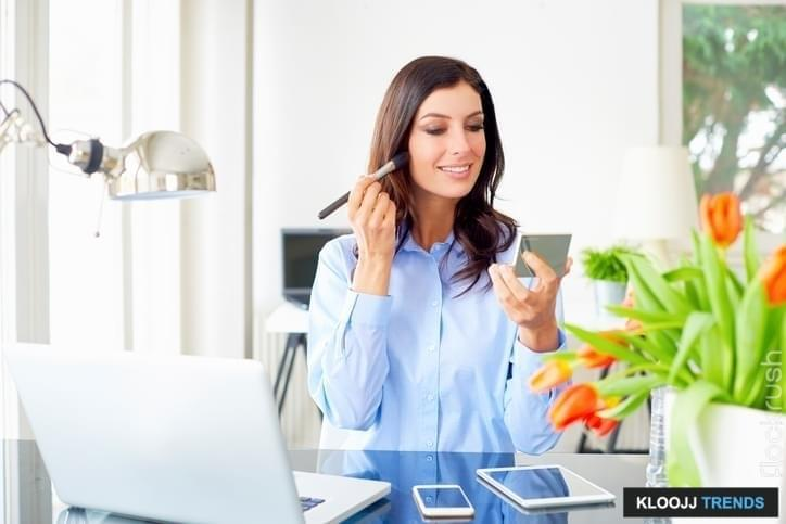 Shot of a smiling young businesswoman sitting in office and apply her makeup while working,