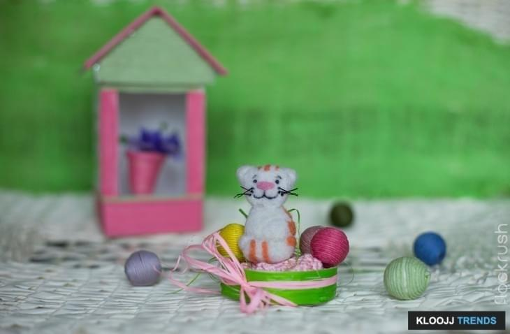Felt a toy cat in a basket with balls. In the background is a decorative house.
