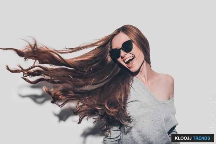 Attractive young smiling woman in sunglasses and with tousled hair looking away while standing against grey background