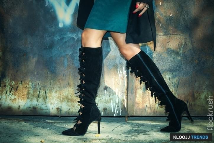 woman legs in black high heel boots  and short skirt outdoor shot against old metal door