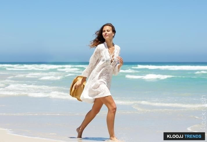 Full length side portrait of a beautiful young woman walking on beach in summer dress