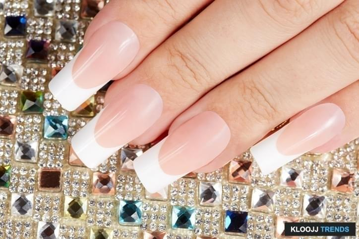 Nails with long artificial french manicure on colorful crystals background