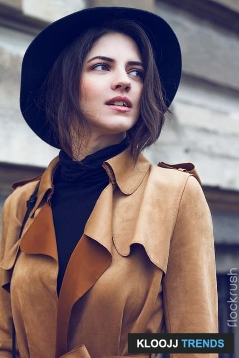 Young beautiful brunette walking and enjoying old city. She is wearing brown coat because is cold. On head she has nice stylish black hat. As an addition she has black handbag.