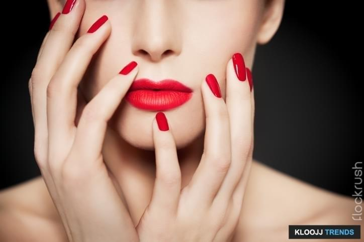 Closeup of face and hands with beautiful manicure and red glossy polish and matte red lipstick.