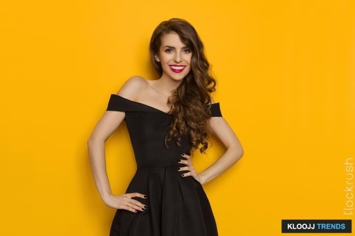 Beautiful young woman in elegant black cocktail dress is holding hands on hip, smiling and looking at camera. Three quarter length studio shot on yellow background.