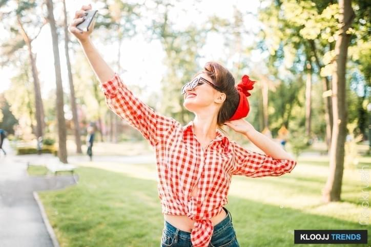 Pinup sexy lady makes selfie on phone camera in park, fifties american fashion. Attractive model in pin up style