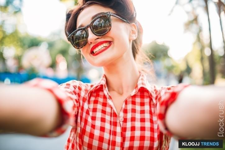 Pinup girl in sunglasses, selfie shot outdoors, fifties american fashion. Attractive model in pin up style