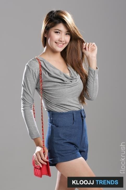 Asian woman pose in long sleeve deep v-neck drape top and high waisted denim shorts.Asian woman pose in long sleeve deep v-neck drape top and high waisted denim shorts.