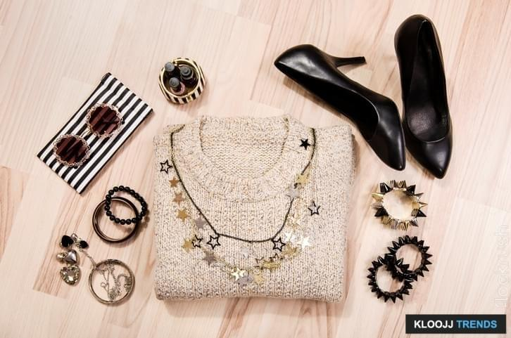 Woman black with gold and silver accessories, high heels, bracelets, necklace and nail polish.