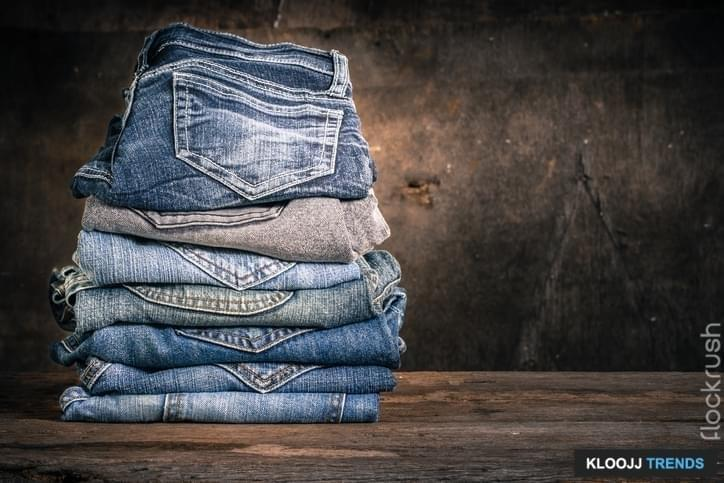 Close up of many jeans trouser stack on wooden vintage background
