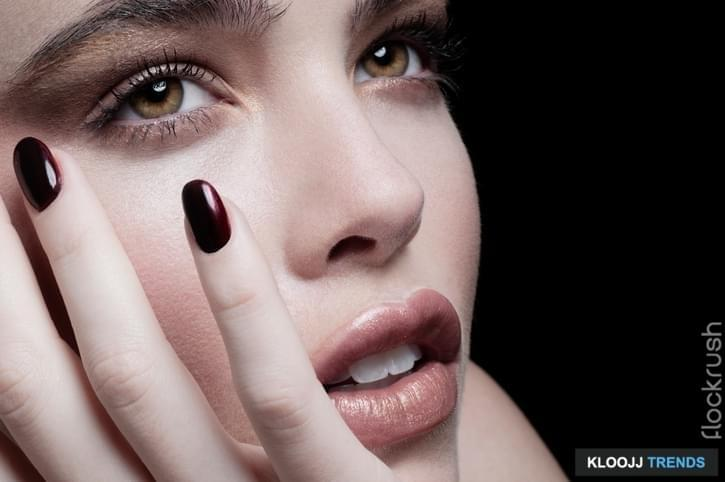 Close-up cropped beauty portrait of Caucasian face with nude toned make-up and blood red nail varnish