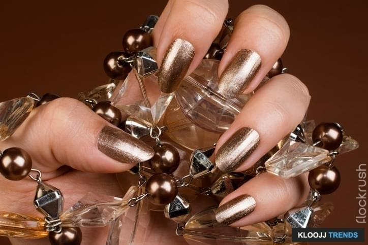 Female hand with glossy brown nails holds necklace with pearls on brown background.