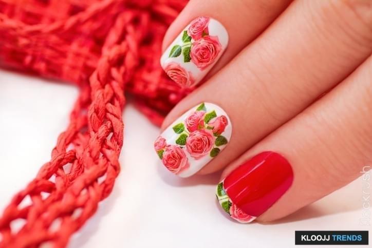 Красный французский маникюр с дизайном из роз на белом фоне.