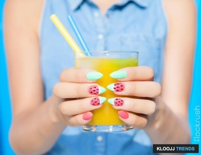 Hands close up of young woman with watermelon manicure holding glass of orange juice, manicure nail art concept