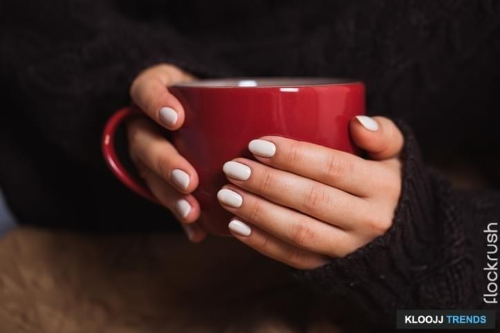 Woman with beautiful manicure holding a red cup of tea