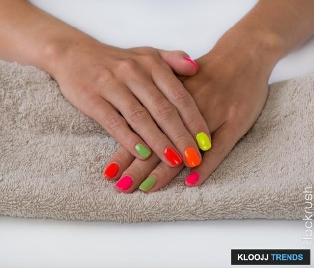 Woman hands with bright and colorful manicure on beige towel