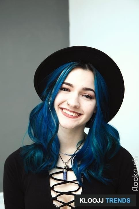 Alternative pretty teenage girl with blue hair and wearing a hat smiling