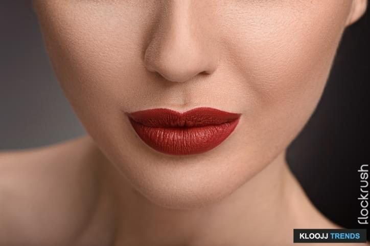 Close up of gorgeous red female lips. Woman has perfect smooth skin