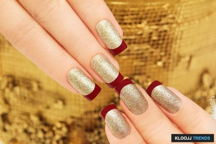 Golden maroon French manicure on woman's hands are rectangular.