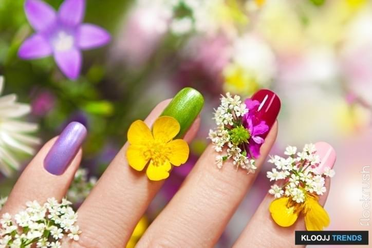Multicolored manicure with natural field and meadow flowers.