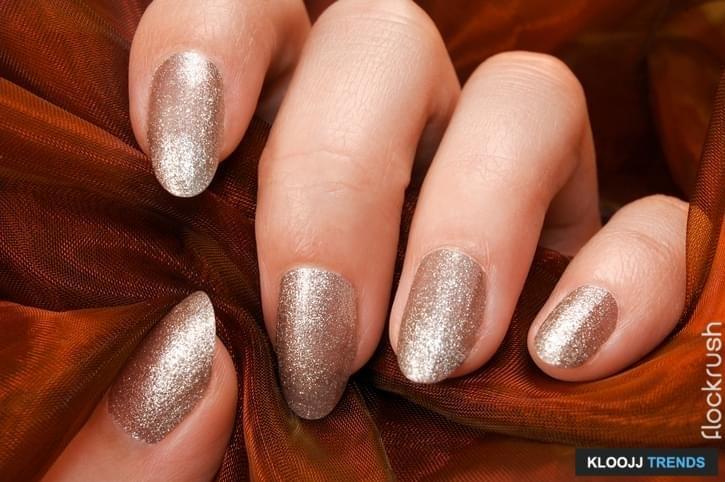 Female fingers with silver nail polish hold orange fabric.