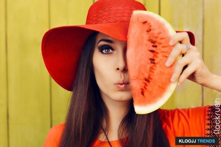 Portrait of a girl holding summertime fruit on green background