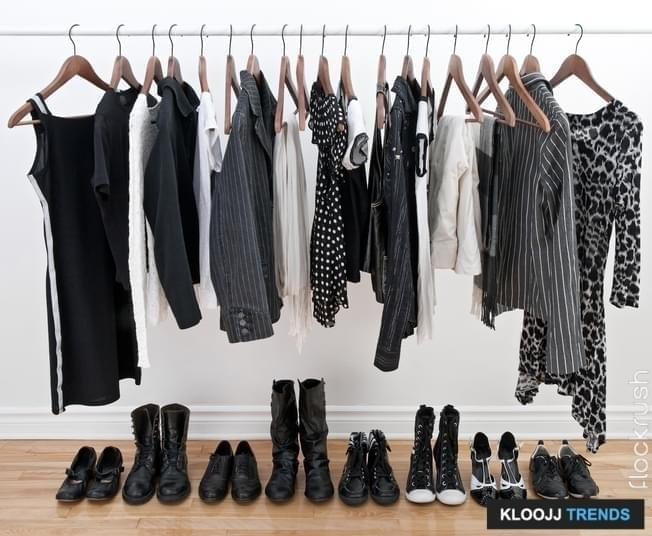 Women's clothing hanging from a metal bar and shoes on the hardwood floor beneath them.  The clothes and shoes are primarily black with some white and gray.  A white wall is in the background.