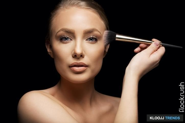 Pretty young woman applying make up with a brush. Beautiful young caucasian fashion model on black background.