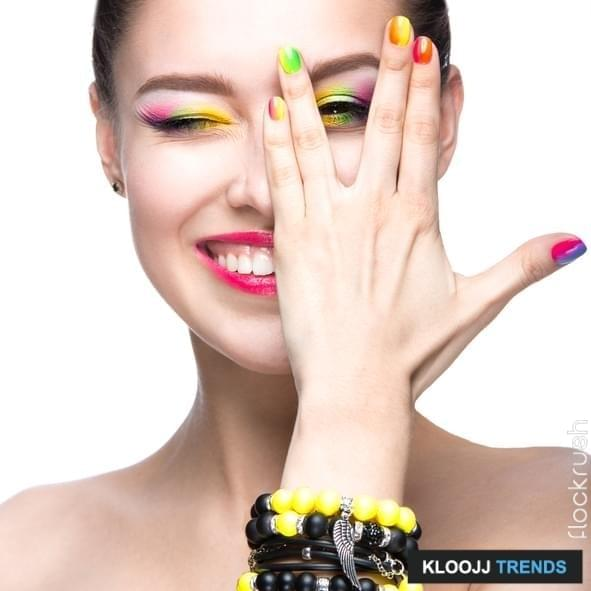 Beautiful model girl with bright colored makeup and nail polish in the summer image. Beauty face. Short colored nails. Picture taken in the studio on a white background.