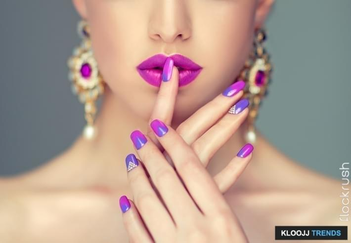 Beautiful woman-model dressed in a big, purple, oriental style earings is showing blue and purple manicure on the nails and magenta color lipstick on the lips. Fashion makeup and cosmetic.