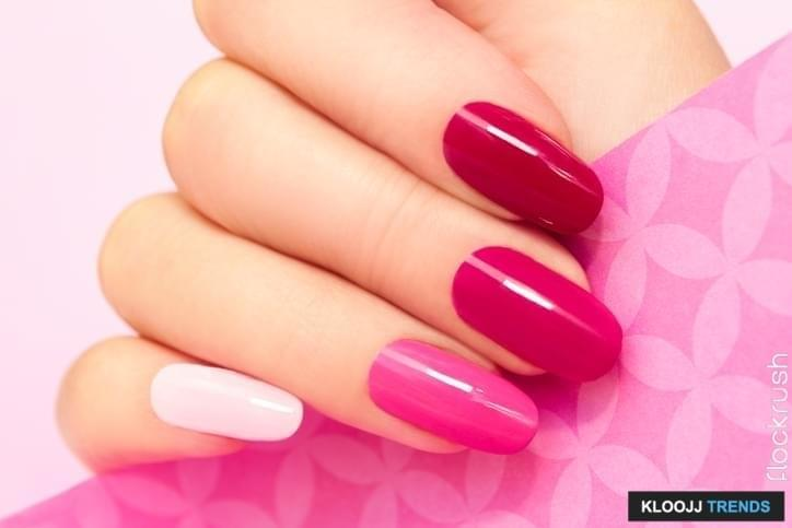 Multicolored manicure with different shades of pink nail Polish on women's hand