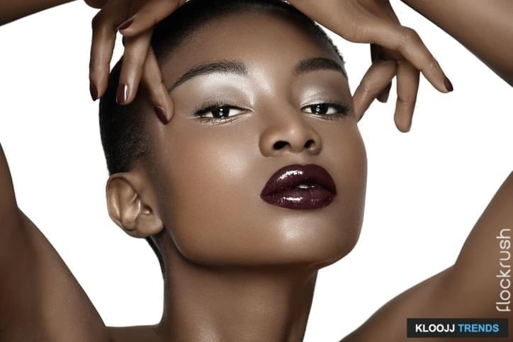 Beautiful African fashion model closeup. Plum lipstick and dark nail polish. Posing over white background.