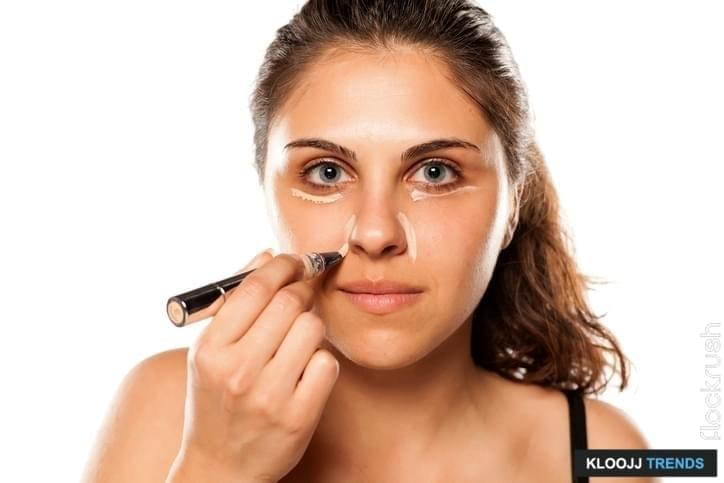 young beautiful woman apply concealer under the eyes and around her nose