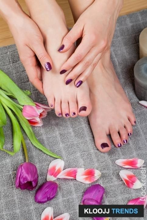 Close up of freshly painted nails done in purple on hands and feet besides loose flower pedals and a lit candle