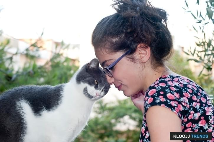Young female posing with her loving cat