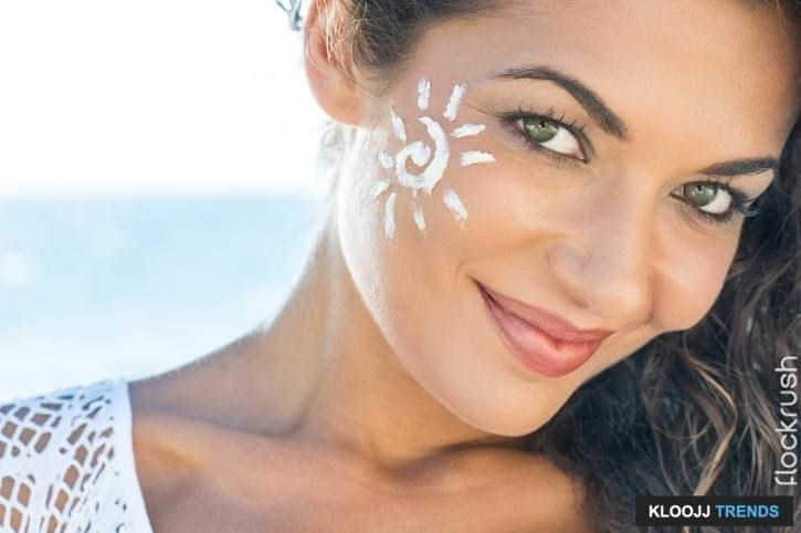 Carefree Young Woman With Suncream On Face At Beach