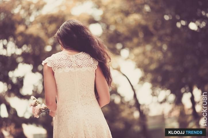 Lady in a lace dress with flowers in her hands, rear view
