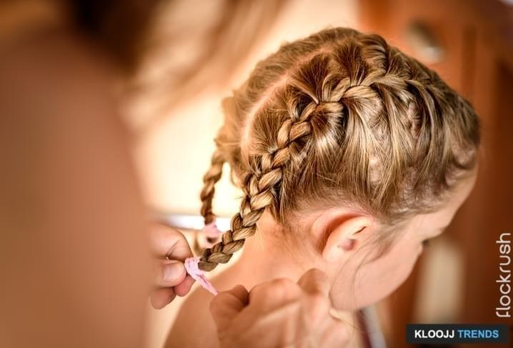 Mother is making of braids on little daughter's head. Hairdresser is braiding the hair on a young girl. Getting ready for school.
