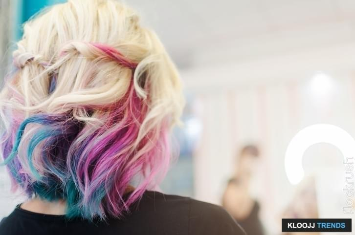 Happy woman in beauty salon with new hairstyle and haircut rainbow or unicorn hair.