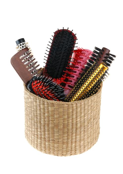 Old hairbrushes and comb in small basket, isolated on white