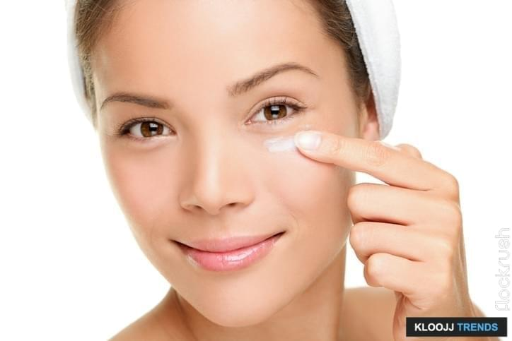 Face cream woman applying skin cream under eyes. Beauty eye contour cream, wrinkle cream or anti-aging skin care cream. Beautiful young mixed race Asian Chinese  beauty model in her 20s isolated on white background. Similar: