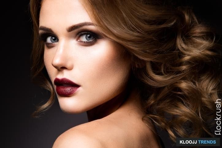 Close-up portrait of beautiful woman with bright make-up and dark red lips
