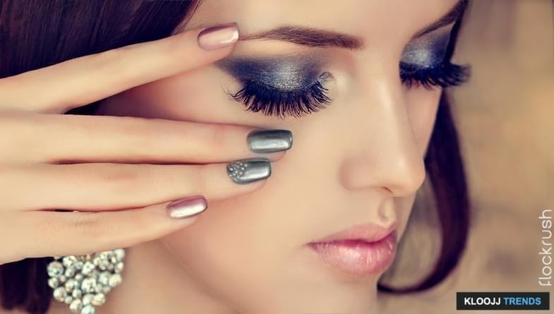 Beautiful woman-model is showing silver and rose manicure on the nails, rose lipstick and smokey eyes style make up. Makeup, cosmetic and posh jewelry earrings.