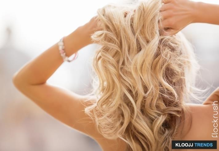 Blonde woman holding her hands in hair. A photo of romantic hairstyle.